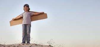 Счастливый мальчик с картонными коробками крылов против мечты неба мухы Стоковая Фотография