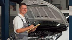 Счастливый механик автомобиля усмехаясь к камере пока заполняющ бумаги стоковое изображение rf