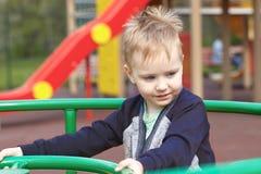 Счастливый милый кавказский белокурый ребенок на игровой площадке, усмехаясь стоковая фотография rf