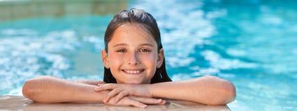 Счастливый милый ребенок девушки усмехаясь в панораме бассейна стоковые фотографии rf