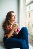 Счастливый милый усмехаясь чай женщины выпивая пока сидящ на windowsill стоковые изображения rf