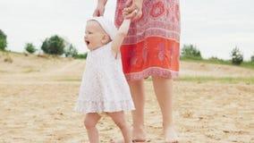 Счастливый младенец делает первые шаги с матерью на песчаном пляже сток-видео