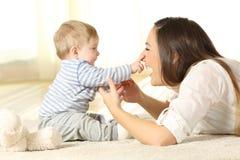 Счастливый младенец касаясь его стороне матери стоковое изображение rf