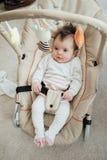 Счастливый младенец ослабляя в стуле хвастуна стоковая фотография