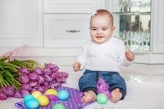 Счастливый младенец сидя в кухне Девушка играя пасхальные яйца жулик Стоковая Фотография