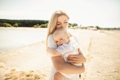 Счастливый младенец huges матери Мать держит ребенка в ее оружиях, младенца обнимая маму, конец-вверх стоковые изображения rf