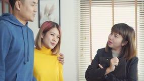 Счастливый молодой азиатский агент пар и риэлтора Жизнерадостный молодой человек подписывая некоторые документы пока сидящ на сто