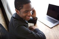 Счастливый молодой африканский бизнесмен сидя на столе с компьютером и говоря на мобильном телефоне Стоковое Изображение