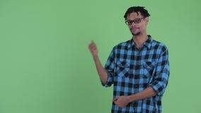 Счастливый молодой африканский человек хипстера показывая что-то и давая большие пальцы руки вверх видеоматериал