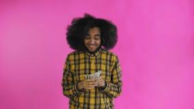 Счастливый молодой Афро-американский человек держа деньги в его руках и смотря камеру на пурпурной предпосылке видеоматериал