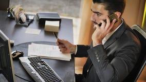 Счастливый молодой бизнесмен на телефоне, сидя на столе стоковое изображение