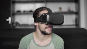 Счастливый молодой бородатый человек битника используя его дисплей шлемофона VR для игры виртуальной реальности или наблюдающ вид