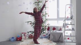 Счастливый молодой брюнет женщина в пижамах стоит около рождественской елки бросает вверх confetti окном движение медленное видеоматериал