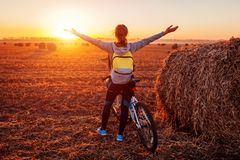 Счастливый молодой велосипедист поднимая раскрытые оружия в поле осени восхищая взгляд Назначение riched женщиной стоковое изображение