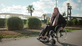 Счастливый молодой женский человек в инвалидной коляске идет в парк в солнечном дне акции видеоматериалы