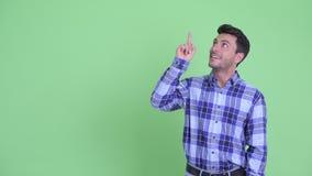 Счастливый молодой испанский человек указывая вверх и давая большие пальцы руки вверх акции видеоматериалы