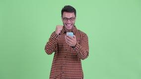 Счастливый молодой испанский человек хипстера используя телефон и хорошие новости получать видеоматериал