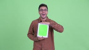 Счастливый молодой испанский человек хипстера показывая цифровой планшет и смотря удивленный акции видеоматериалы