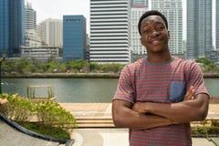 Счастливый молодой красивый африканский человек с оружиями пересек в город стоковое изображение rf