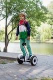 Счастливый молодой мальчик балансируя на электрическом hoverboard Стоковое Изображение RF