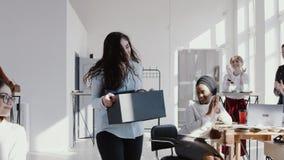 Счастливый молодой менеджер смешанной гонки женский входя в современный офис с коробкой, приветствованной ЭПОПЕЕЙ замедленного дв сток-видео