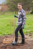Счастливый молодой мужчина с лопаткоулавливателем и деревянной коробкой с картошкой саженца Стоковое Фото