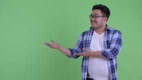 Счастливый молодой полный азиатский человек хипстера показывая что-то и давая большие пальцы руки вверх акции видеоматериалы