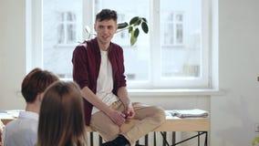 Счастливый молодой работник компании запуска сидя на таблице на современном офисе просторной квартиры слушая семинар говоря с кол акции видеоматериалы