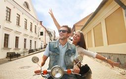 Счастливый молодой самокат катания пар в городке Красивое перемещение парня и молодой женщины Концепция приключения и каникул Стоковые Изображения