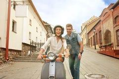 Счастливый молодой самокат катания пар в городке Красивое перемещение парня и молодой женщины Концепция приключения и каникул Стоковые Изображения RF