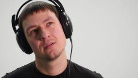 Счастливый молодой человек в наушниках танцуя и слушает музыка на белой предпосылке акции видеоматериалы