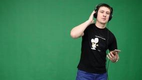 Счастливый молодой человек в наушниках танцуя и слушает музыка на зеленой предпосылке видеоматериал