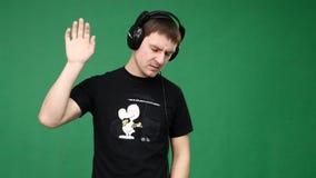 Счастливый молодой человек в наушниках танцуя и слушает музыка на зеленой предпосылке акции видеоматериалы