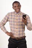 Счастливый молодой человек в рубашке держа мобильный телефон стоковые изображения rf