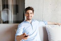 Счастливый молодой человек держа дистанционное управление ТВ Стоковые Фотографии RF
