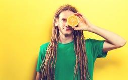 Счастливый молодой человек держа половины апельсина Стоковое Изображение RF