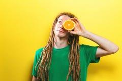 Счастливый молодой человек держа половины апельсина Стоковая Фотография