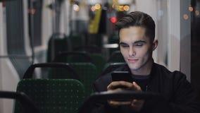 Счастливый молодой человек используя смартфон пока трамвай катания, снятое steadicam движение медленное сток-видео