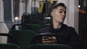 Счастливый молодой человек используя смартфон пока трамвай катания, снятое steadicam движение медленное видеоматериал