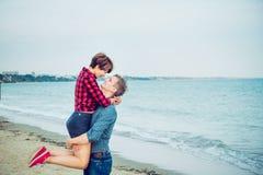 Счастливый молодой человек нося его женщину на пляже Пары наслаждаясь днем, имеющ потеху Парень и подруга имея дату Концепция стоковая фотография