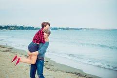 Счастливый молодой человек нося его женщину на пляже Пары наслаждаясь днем, имеющ потеху Парень и подруга имея дату Концепция стоковые фото