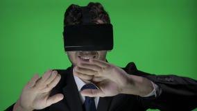 Счастливый молодой человек нося официально костюм с стеклами vr 3d для того чтобы перечислить и напечатать внутри виртуальное про акции видеоматериалы