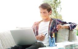 Счастливый молодой человек работая с компьтер-книжкой от дома Стоковые Фото