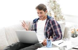 Счастливый молодой человек работая с компьтер-книжкой от дома Стоковая Фотография RF