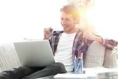 Счастливый молодой человек работая с компьтер-книжкой от дома Стоковое Изображение