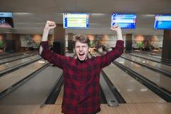 Счастливый молодой человек сделал забастовку боулинга Студент поднял его руки от утехи пока играющ боулинг Победа боулинга стоковые изображения