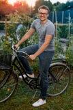 Счастливый молодой человек с велосипедом в парке С стеклами для визирования на заходе солнца Стоковое фото RF
