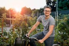 Счастливый молодой человек с велосипедом в парке С стеклами для визирования на заходе солнца Стоковые Фото