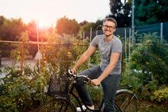 Счастливый молодой человек с велосипедом в парке С стеклами для визирования на заходе солнца Стоковые Изображения