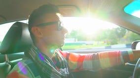 Счастливый молодой человек управляя автомобилем на небе захода солнца на на открытом воздухе взрослые молодые Закройте вверх усме сток-видео